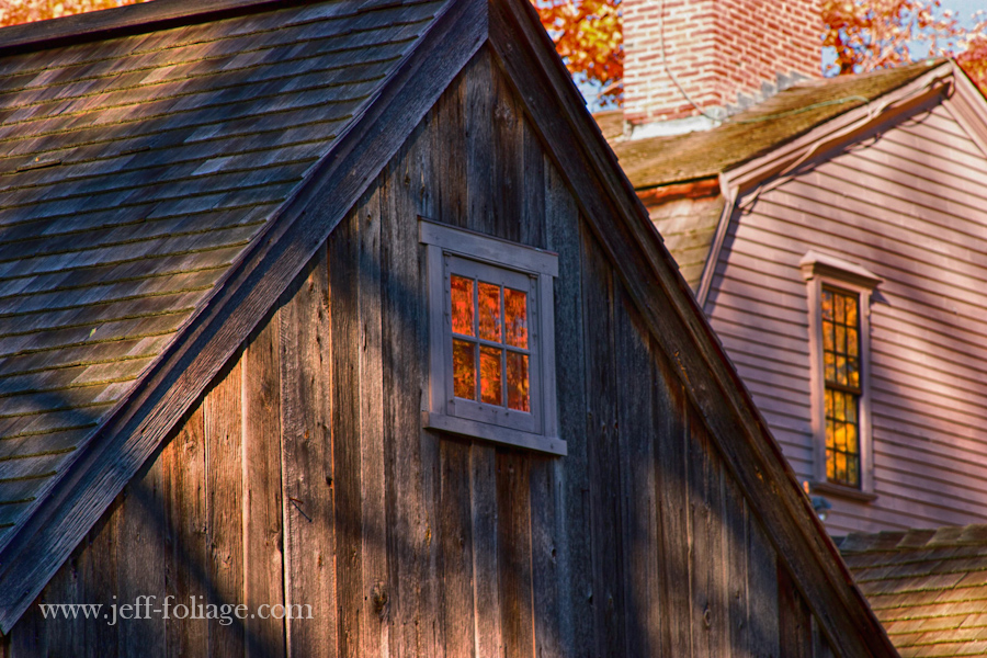 A window in the Old Manse reflects the orange fall colors in the windows