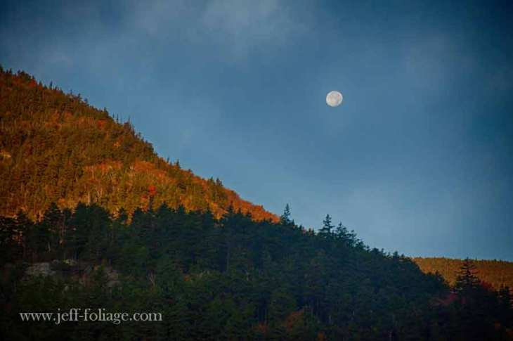 Moon setting over the fall foliage of the beaver pond and Woodstock New Hampshire
