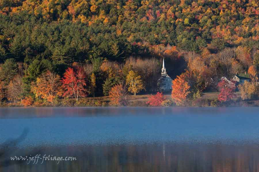New Hampshire fall foliage rises above a little white church in Eaton NH.