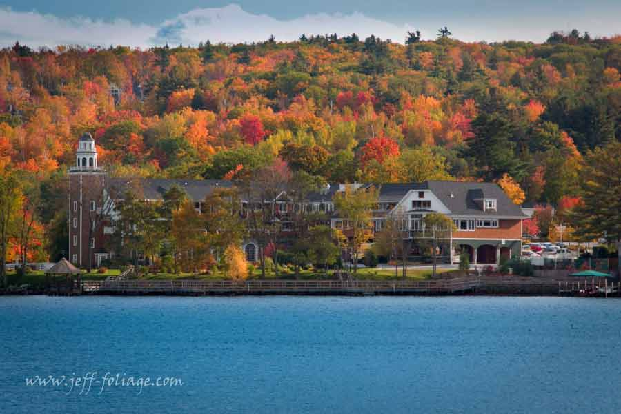 a loon in the water looks on churches landing in Meredith New Hampshire on Lake Winnipesaukee amid all the beautiful fall colors of a New England's autumn