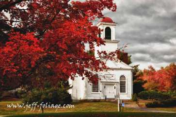 Small white New Hampshire church surrounded by bright red fall foliage in New England.