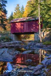 Stoney Brook Covered Bridge with fall colors reflected in the water of the stream passing below