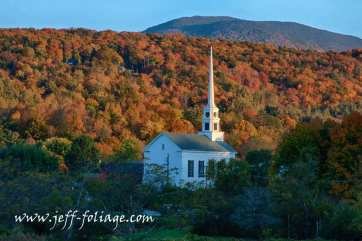 Fall colors around a small white church in Stowe Vermont