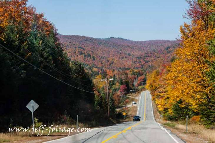 The road in Maine leads to Errol NH. The hills are covered with peak fall colors for New England.