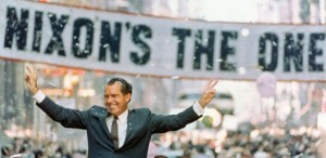 "Nixon giving the peace sign in front of banner that reads ""Nixon's The One"""