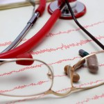 Glasses and a stethoscope laying atop a heart monitor read out