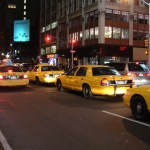 Yellow cabs lined up on a NY street at night