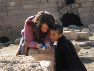 Steph looking at photos with a local kid in Harran