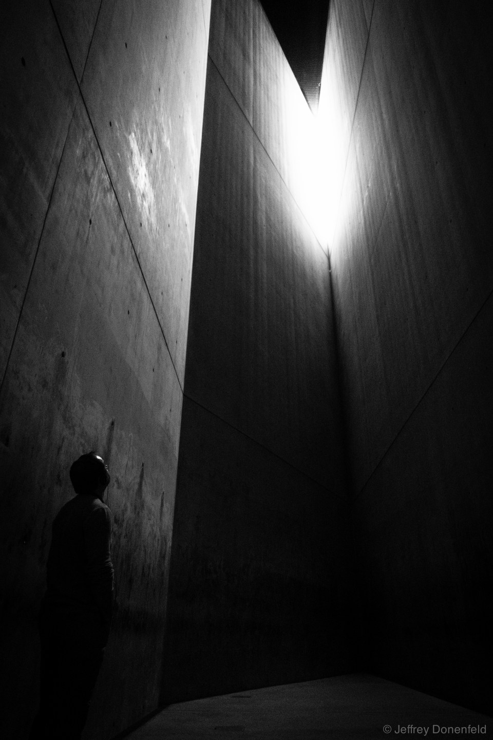 "Jewish Museum, Berlin. This is the Holocaust Tower. From Wikipedia: ""The first axis ends at a long staircase that leads to the permanent exhibition. The second axis connects the Museum proper to the E.T.A. Hoffmann Garden, or The Garden of Exile, whose foundation is tilted. The Garden's oleaster grows out of reach, atop 49 tall pillars. The third axis leads from the Museum to the Holocaust Tower, a 79 foot (24 m) tall empty silo. The bare concrete Tower is neither heated nor cooled, and its only light comes from a small slit in its roof."""