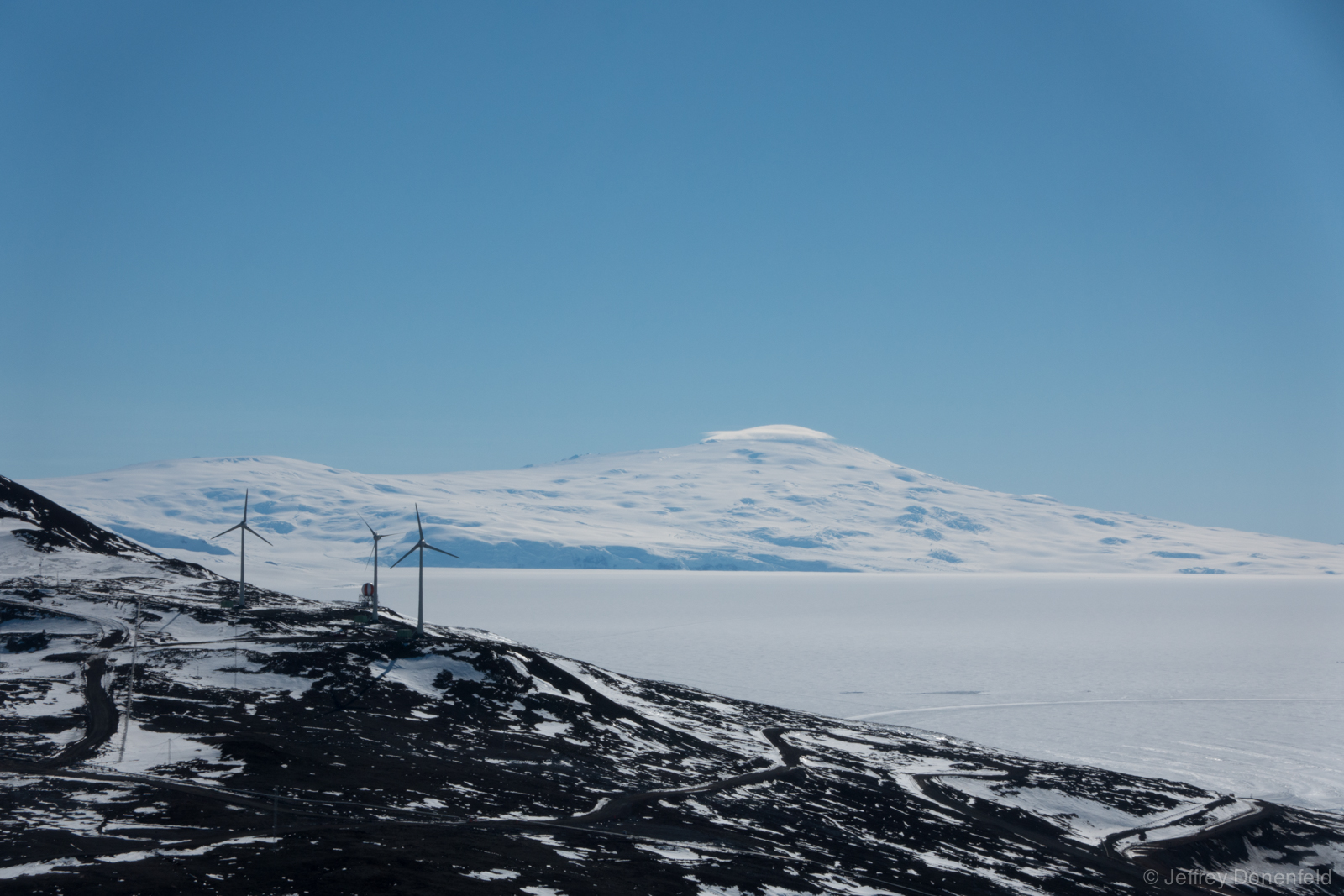 Looking north from Observation Hill, wind turbines are visible, as well as Mt. Terra Nova on the left and Mt. Terror on the right capped by a lenticular cloud.
