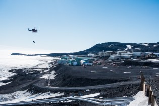 A Bell 212 Twin Huey comes in to drop off a slingload of gear at McMurdo Station.