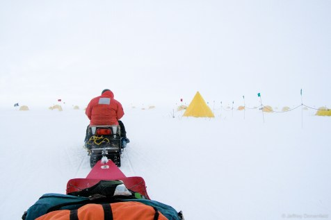 "After a successful landing at field camp and quick briefing in the galley, first order of business was to get our tents and gear setup. In this picture, I'm sitting in our gear sled as we snowmobile to ""Tent City"", on the edge of camp. Everybody has their own tent, and it's a blend of 4-season mountaineering tents, pointy ""scott tents"", and dome-shaped ""Arctic Oven"" tents."