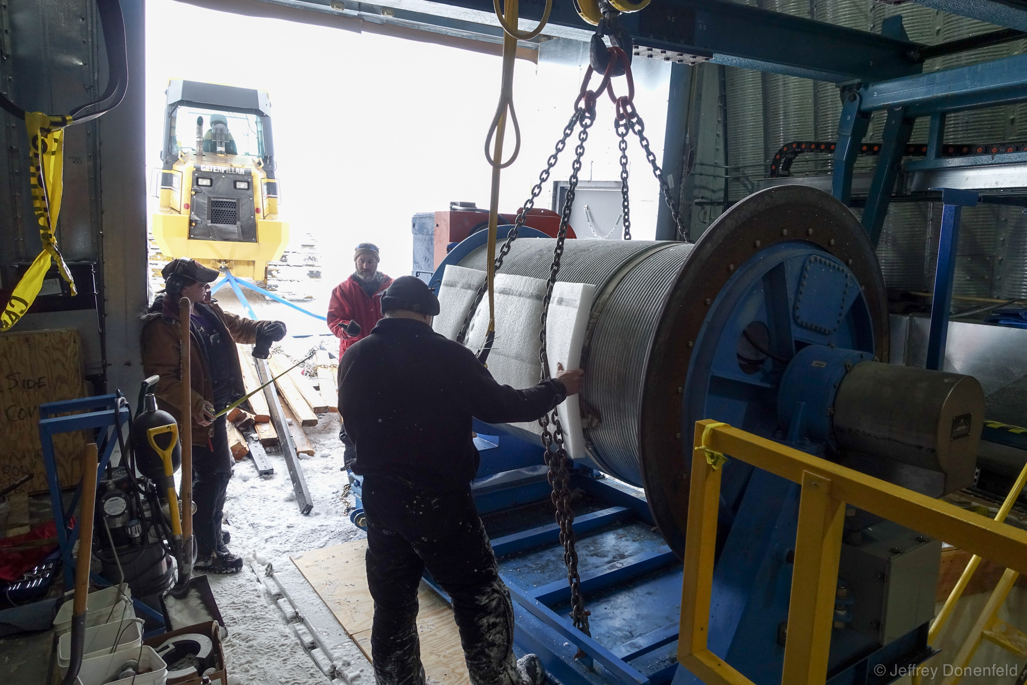 Finally, the large winch reel is hoisted out of the pit - next step is to drag it up the ramp to the surface, where it gets staged for air transport.