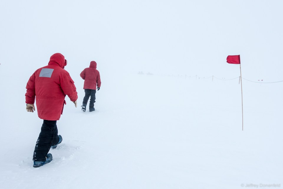 Walking back to WAIS Divide Field Camp after a day working in the drill arch. On days of low visibility, flags are the only way to tell which way to walk - and where the ground is.