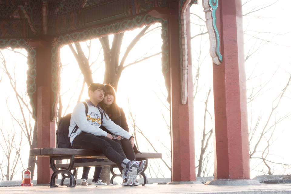 A happy couple in a romantic pavilion underneath the N Seoul Tower.