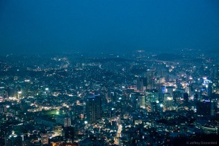 Seoul at night, seen from the N Seoul Tower. Seoul is electric, with colorful lights stretching off into the smog.