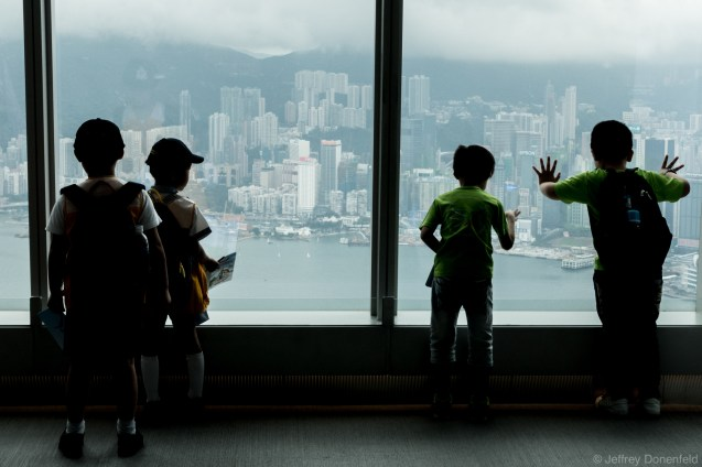 Kids look into Hong Kong from the observation deck of the International Financial Center, one of the tallest buildings in the world.