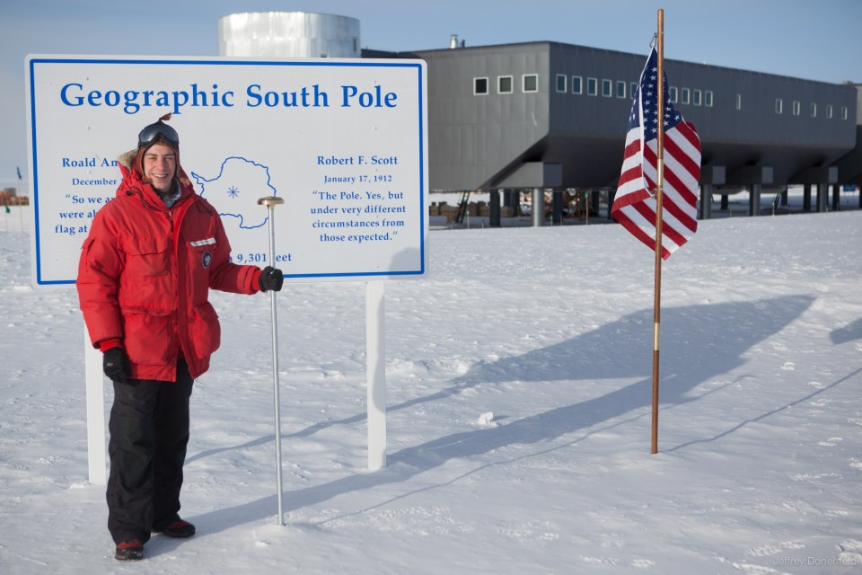The author standing at the Geographic South Pole, Antarctica, with the Amundsen-Scott South Pole Station in the background. 2012.
