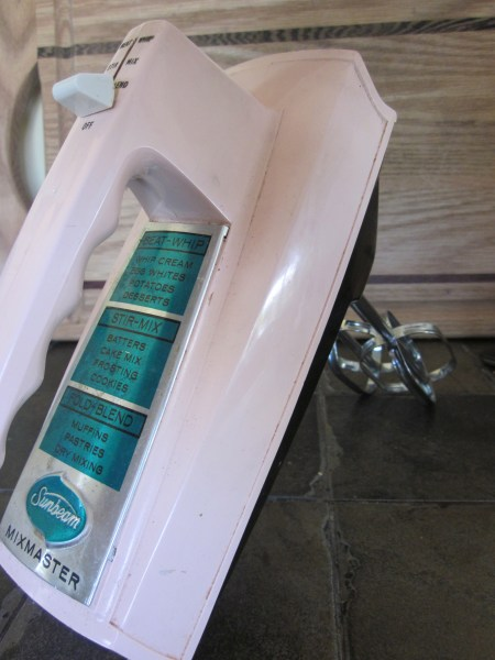 This is a picture of a pastel pink vintage hand mixer made by Mixmaster. It has a metal turquoise label.