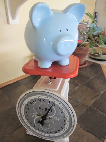 This is an antique kitchen scale with a blue piggy bank on it.