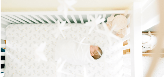 Overhead view of newborn baby asleep in crib