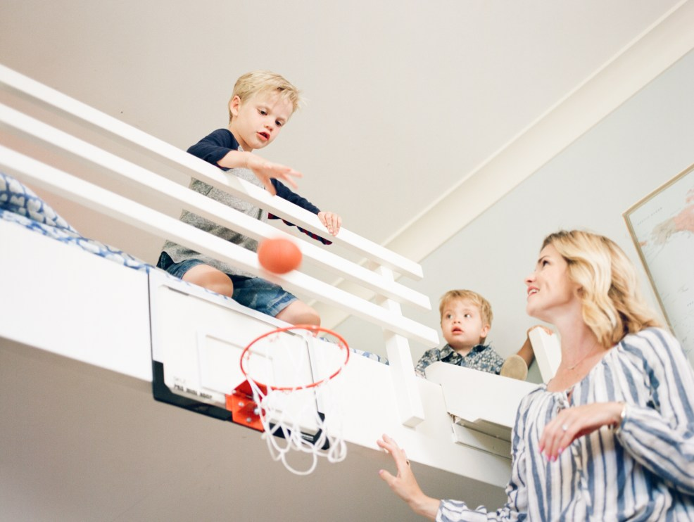 mom with boys in bedroom and boy is dropping a ball through basketball hoop