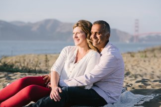 Man and woman sit on beach in front of Golden Gate Bridge
