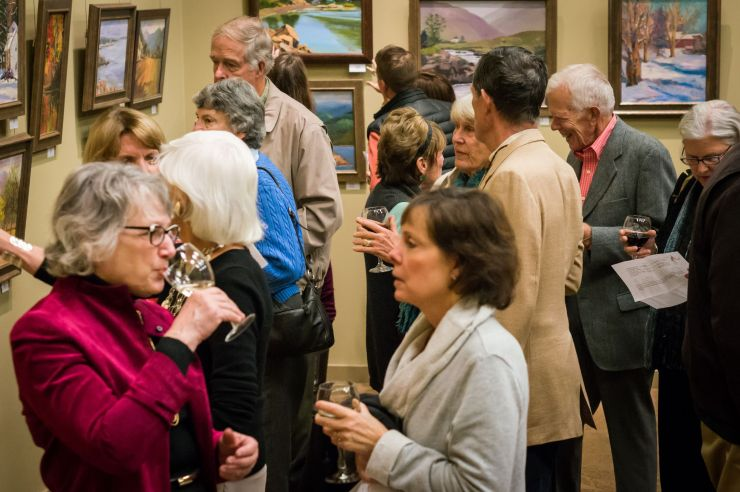 A group of 14 people enjoying wine and conversation while looking at artwork during an opening reception in the John J. Willaman Education Center.