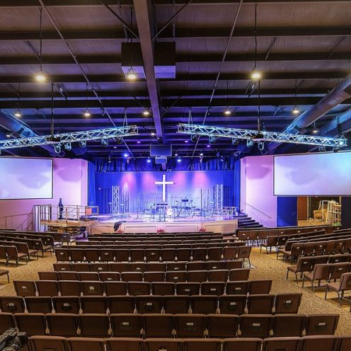 Brightly lit modern church sanctuary with seating and stage
