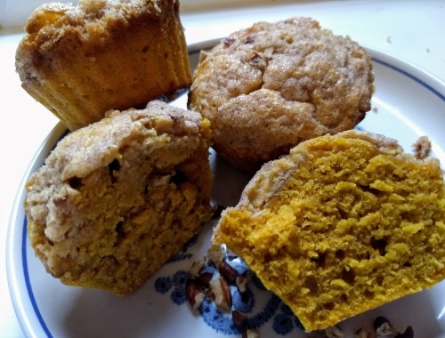 plate of pumpkin cream cheese muffins, cut open to show orange middle.