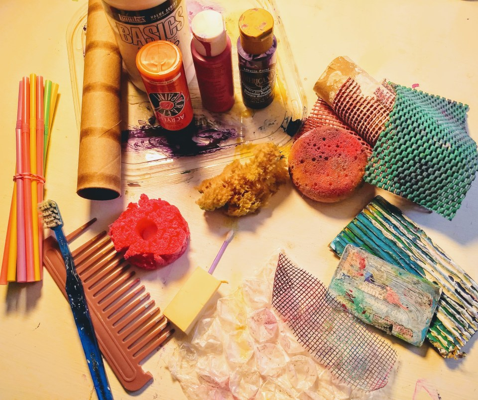 Art Journal Page, recycled materials, craft paints, sponges, gift card, comb, toothbrush, straws, cabinet lining, drywall tape, cardboard, cardboard rolls, gesso, bubble wrap.