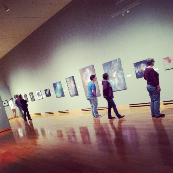 Workshop attendees examining art.