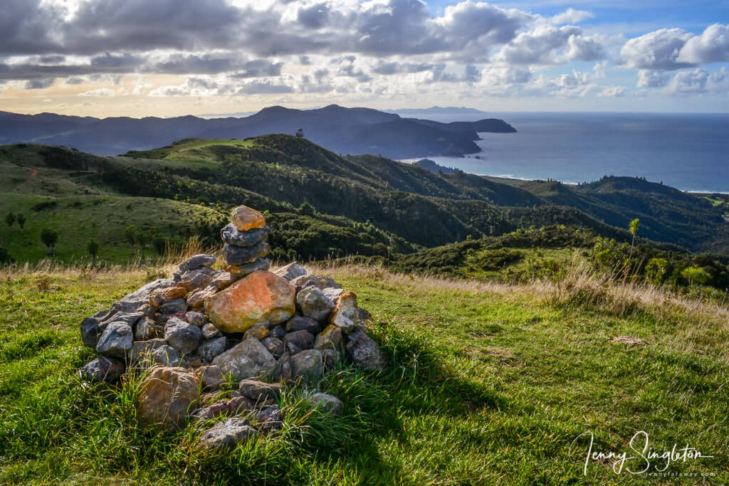 A stone cairn sits atop a hill at the highest point on the Matamataharakeke Track, overlooking Waikawau Bay.
