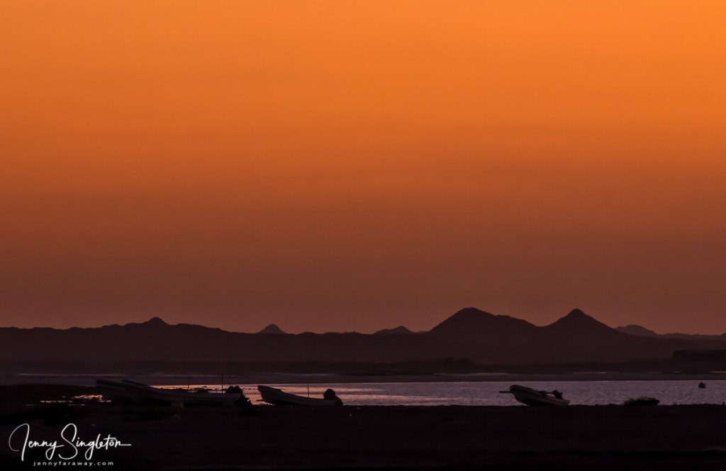 The sky turns orange at sunset on Masirah Island, with silhouettes of mountains and boats.
