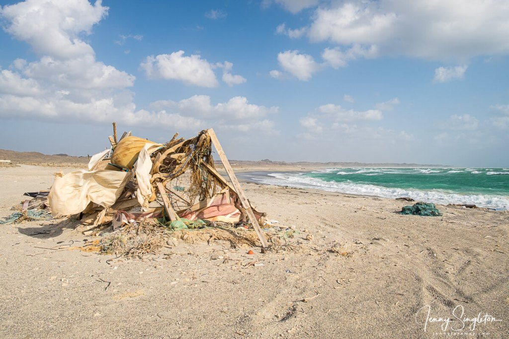 A fishing shack made from random found materials sits on a beach with big green waves on Masirah Island, Oman