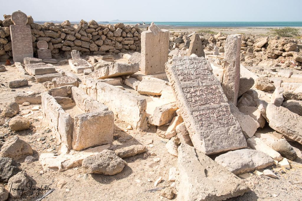 Engraved gravestones are encircled by a stone wall on Masirah Island