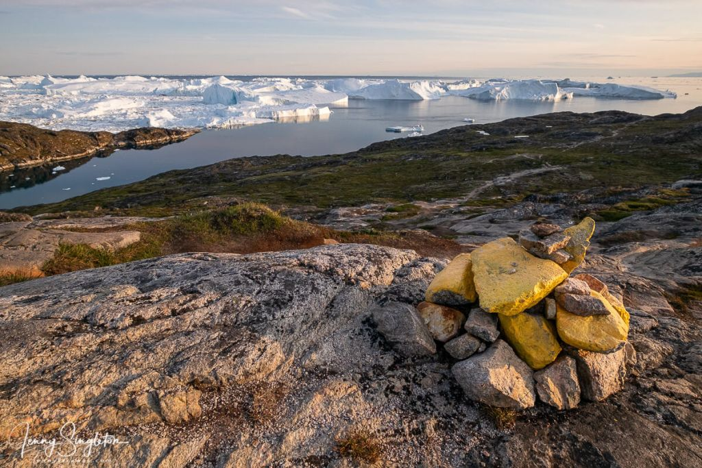 A stone cairn painted yellow to mark the trail, overlooking the small bay formed by land and the icebergs of Ilulissat Icefjord.