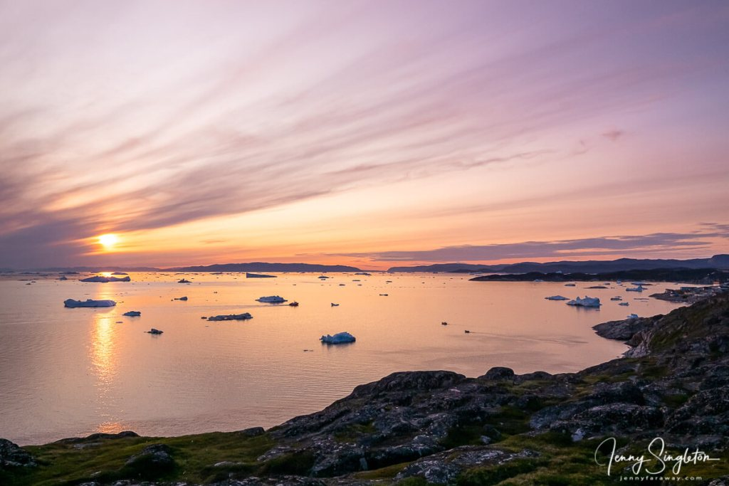 The sun hovers near the horizon, creating a soft pink glow as clouds sweep across the sky over Disko Bay, Ilulissat.