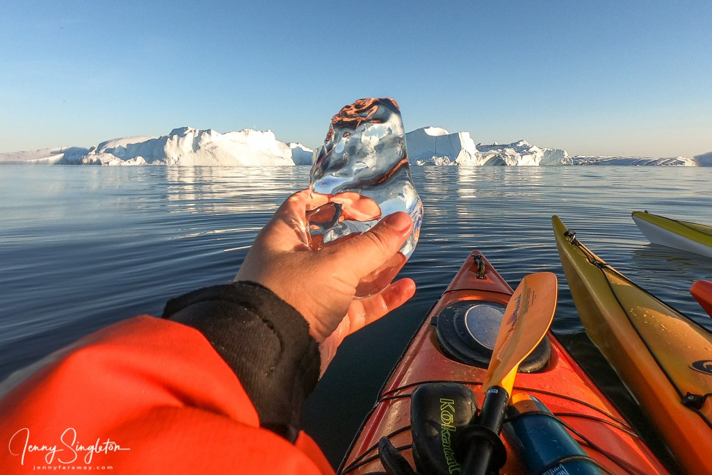I am holding up a piece of black (clear) ice in front of the Ilulissat Icefjord.