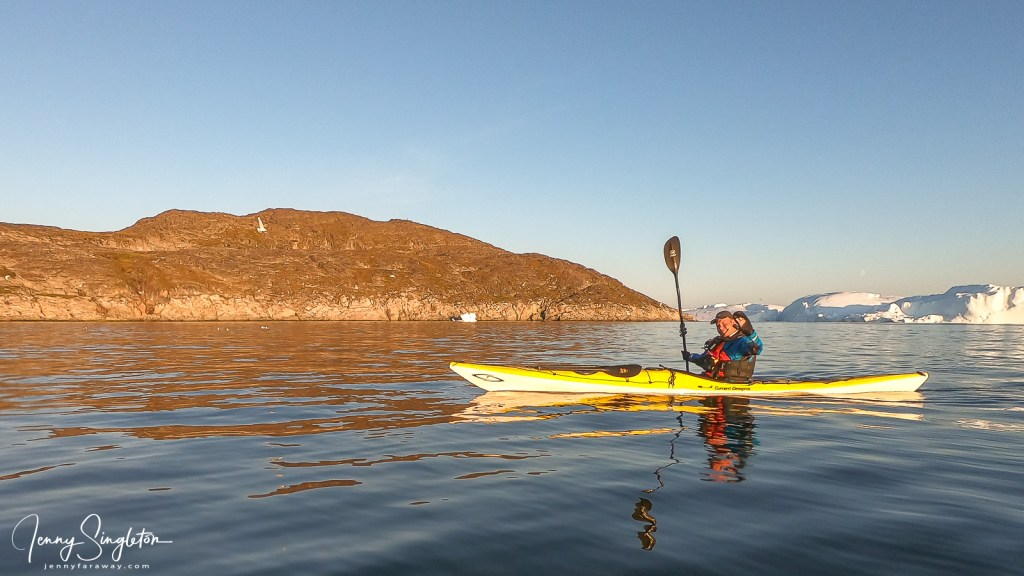 My guide waves hello from his kayak in Disko Bay, Greenland