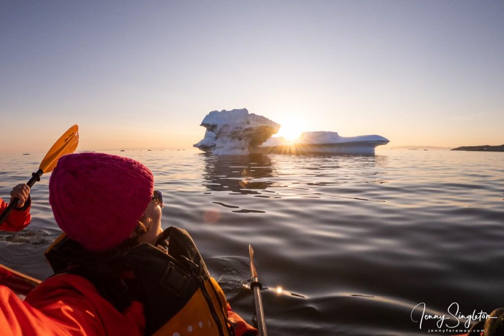 I am looking at the sun setting behind an iceberg in Disko Bay, Greenland