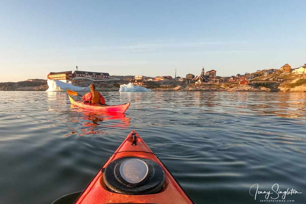 Two kayaks approach the town of Ilulissat, Greenland, with a couple of icebergs in front of them.