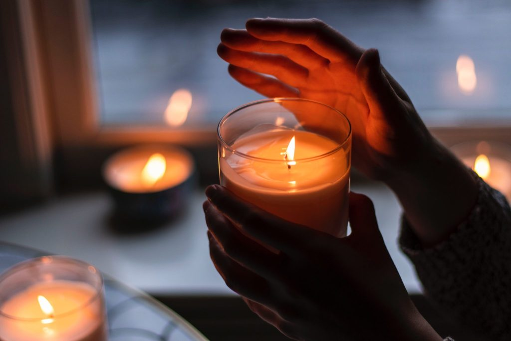 person holding a lit candle with several candles in the background