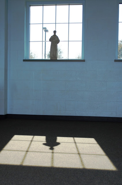 The shadow of St. Francis inside the kids' school gymnasium. Lord make me an instrument...