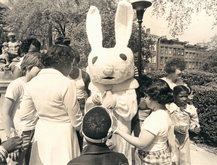 Children gather with an Easter Bunny with astonishingly odd ears on historic Charles Street, 1975