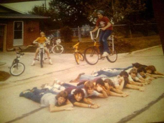 Boys in the San Fernando Valley of California form a human ramp over which their buddy jumps while riding a banana seat bike.