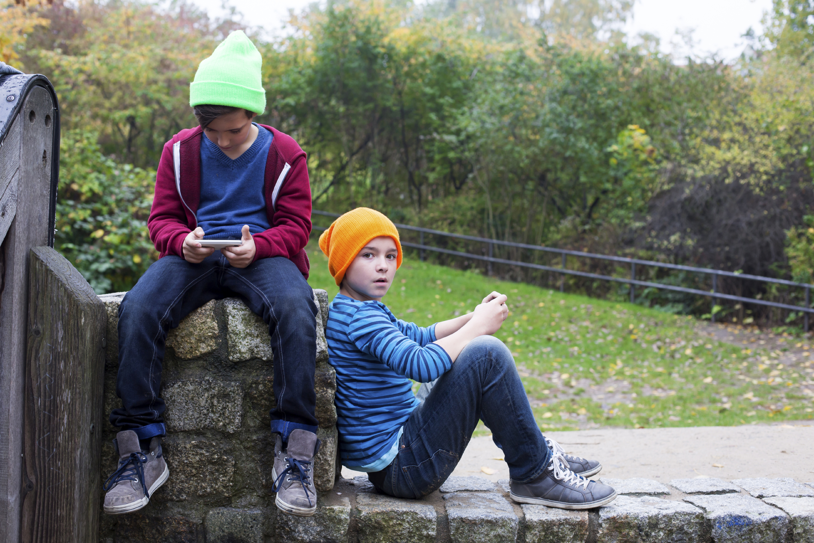 two young boys sitting outside and playing with their phones