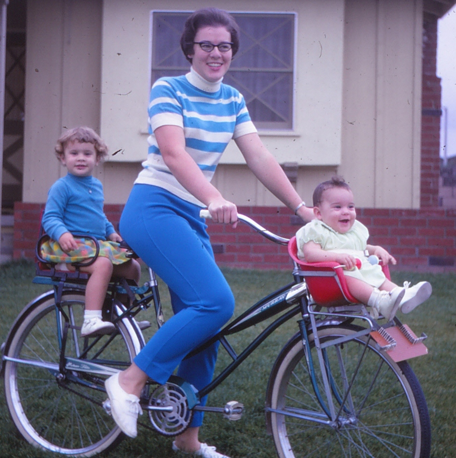 A mother rides a 1960s Murray bicycle with her two children, an Amy and a Jennifer, who sit in vintage children's bicycle seats. From Nelson's Photo Collection. ALL RIGHTS RESERVED.