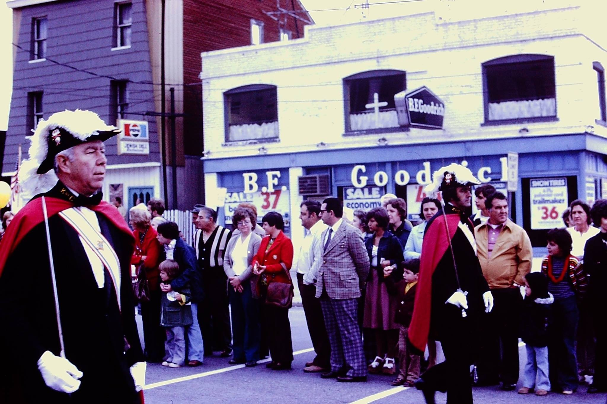 A crowd stands in front of the B.F. Goodrich Store in Newburgh, New York as they await the parade.