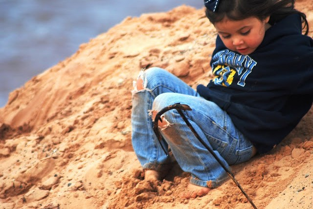 Little girl playing in the sand on the beach on a cool fall day.